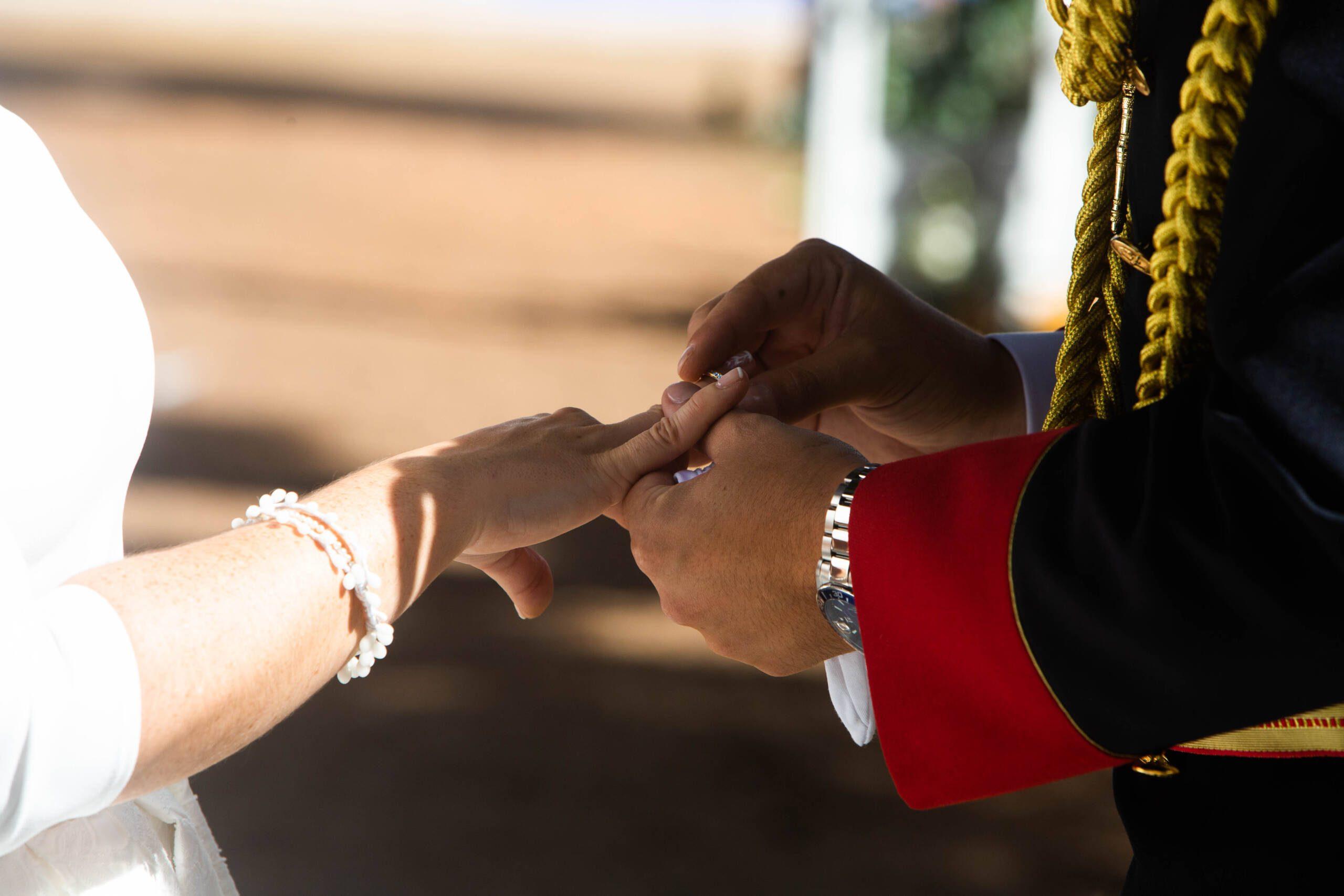 Novio poniendo el anillo a la novia.
